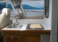 Starboard galley with stainless sink, stainless fridge, 40G freshwater holding tank and white shalestone laminate counter tops