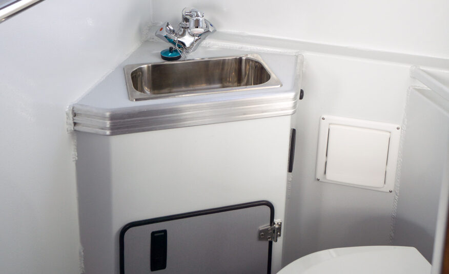 Stand up enclosed head with flush toilet, stainless sink, macerator pump with optional hot water and shower
